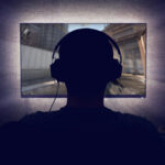 person in gaming headphones looking at a screen, playing a video game.