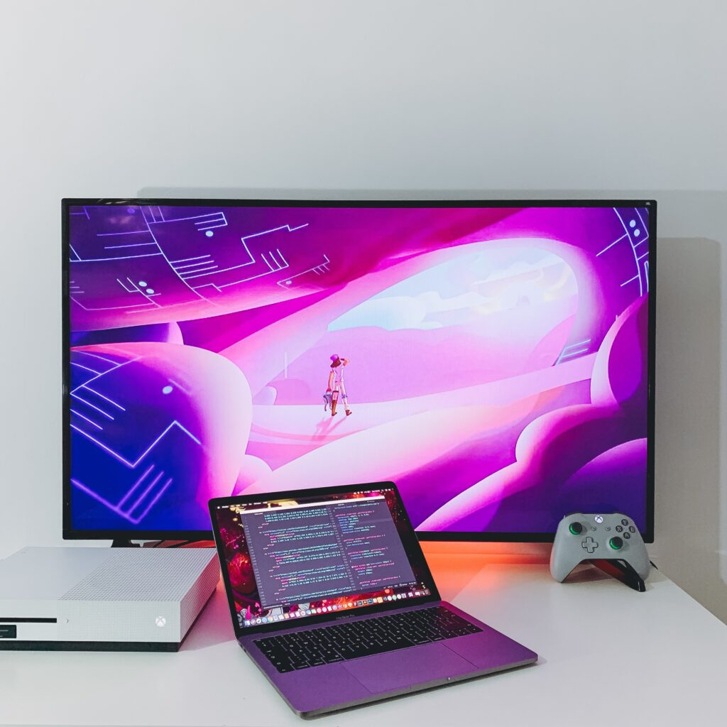 A video game console on a monitor with a controller and laptop in front