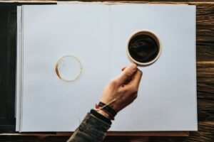 someone holding a cup of coffee over a blank notebook with a coffee stain on it