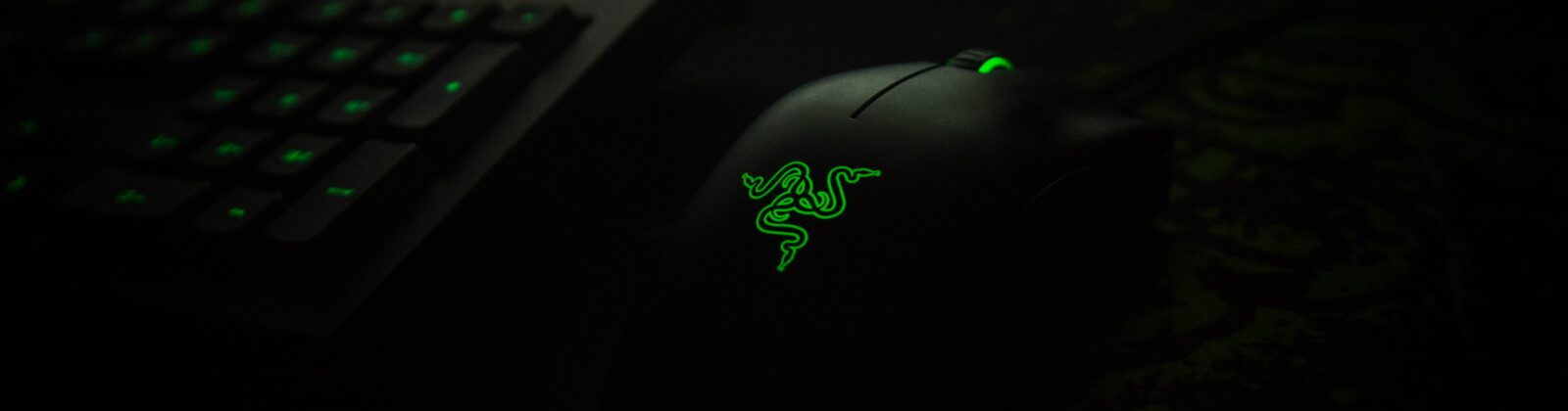 A green gaming mouse and keyboard glowing in the dark