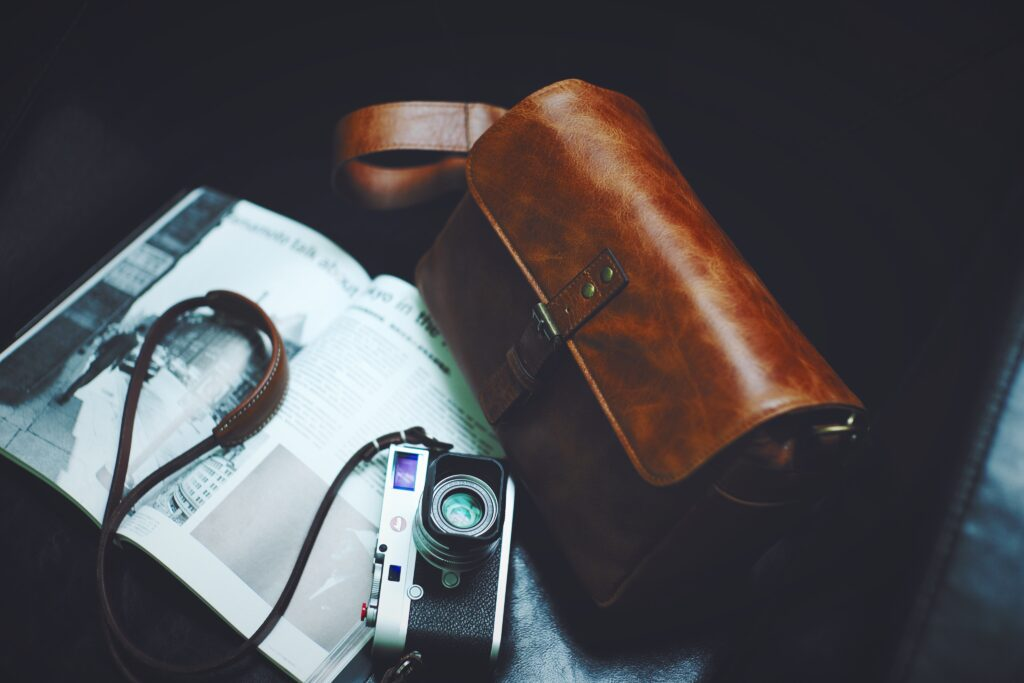 a brown leather bag and a leica camera on a newspaper