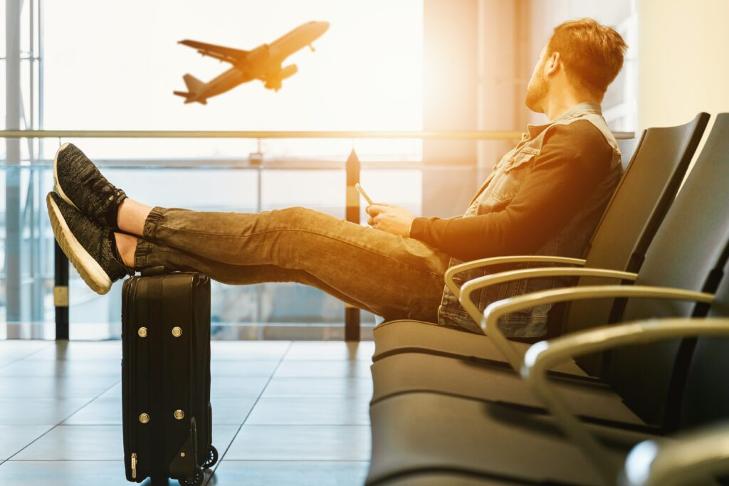 a man in an airport terminal with an airplane taking off in the background