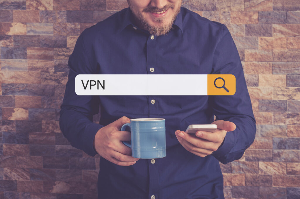 man holding coffee mug searching VPN on his phone