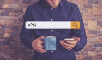 man holding coffee mug searching VPN on his phone