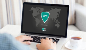 man typing at keyboard with monitor that has a green VPN logo on it