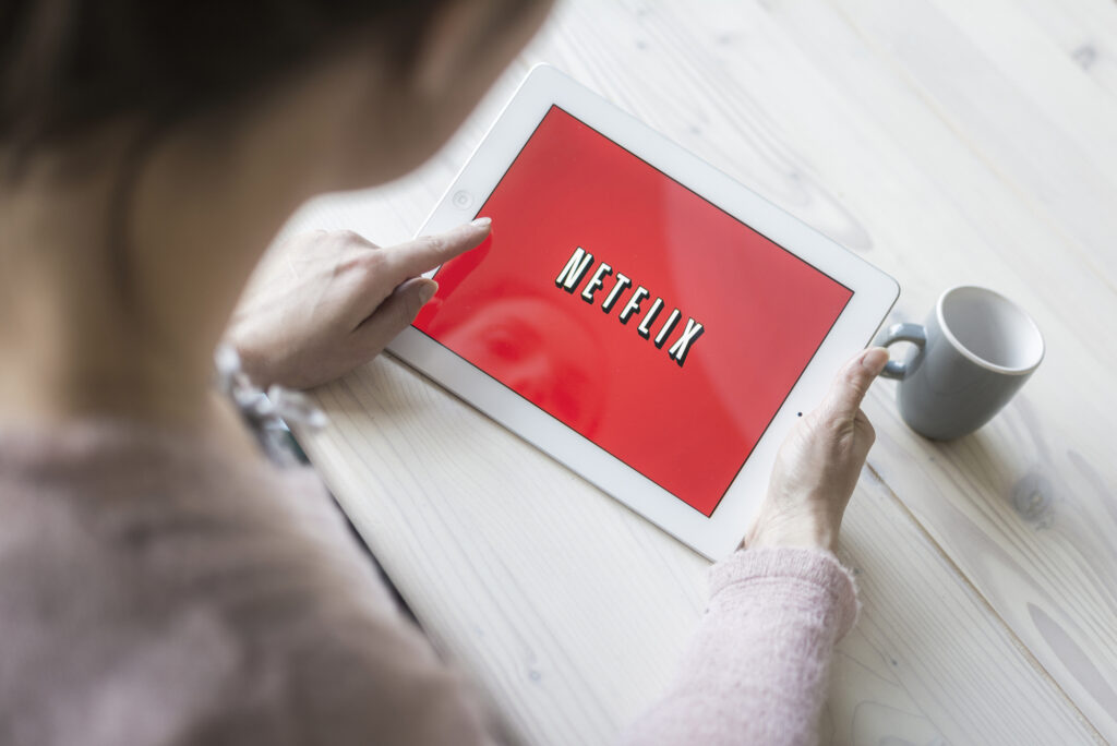 Person holding tablet showing netflix logo