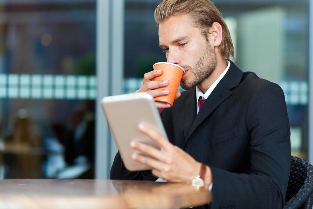 man sipping coffee while looking at his tablet
