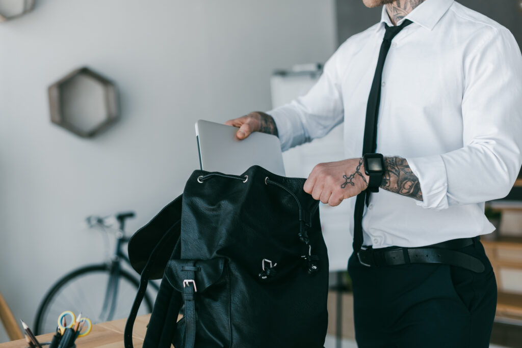 man in dress shirt and tie putting laptop into a black backpack