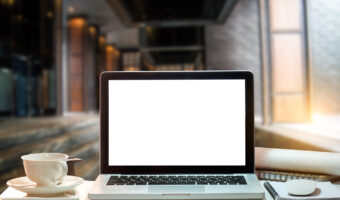 shot of laptop with blank white screen and coffee mug sitting next to it