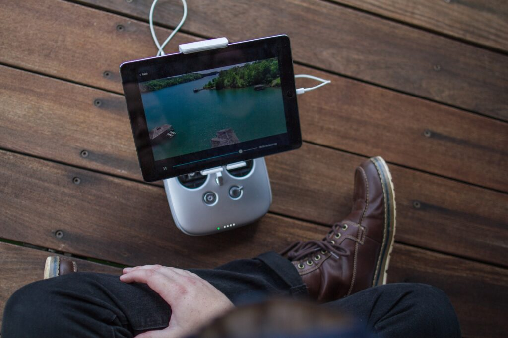 person sitting on the floor looking over an ipad on a portable mount