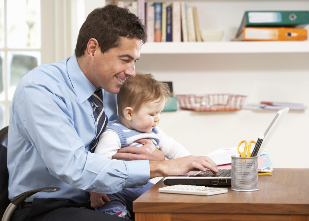 man with baby on his lap working on a laptop from home
