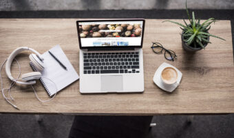 top down view of standing desk with laptop, headphones, coffee mug, and small plant