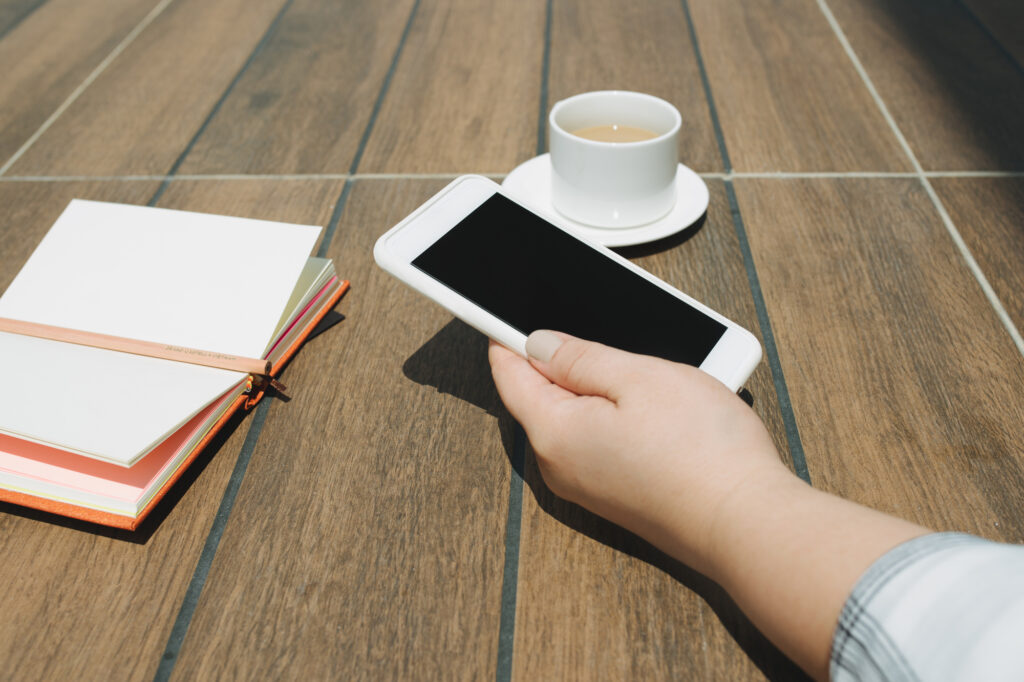 hands holding white mobile phone with blank black desktop screen with notebook and coffee cup on wooden table in cafe