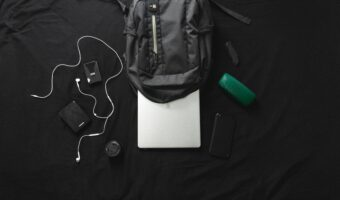 backpack sitting on black desk surrounded by headphones, gadgets, and office supplies, with laptop coming out the top of the backpack.