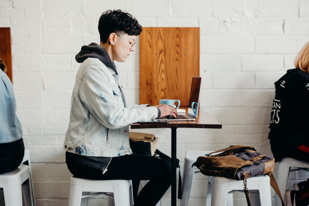 person sitting at desk working on laptop with laptop backpack sitting on floor next to them.