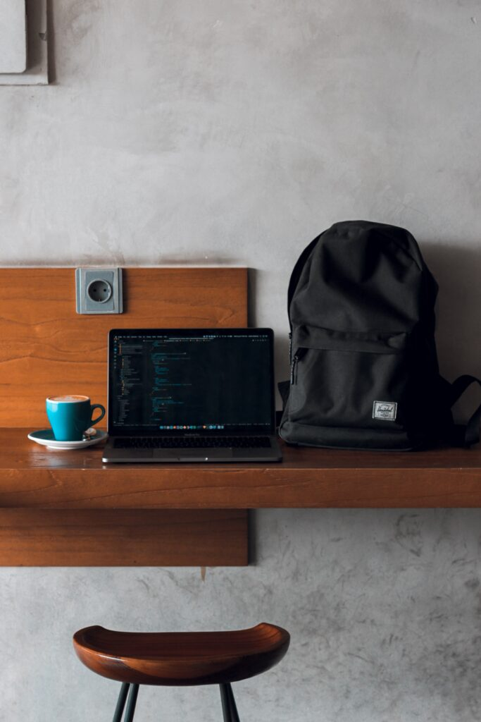 laptop sitting on desk next to laptop backpack and cup of coffee