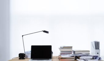laptop sitting on desk with lamp and stack of books