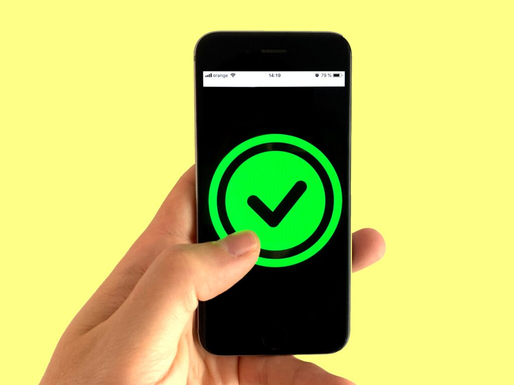 person holding phone with giant green checkmark on the screen