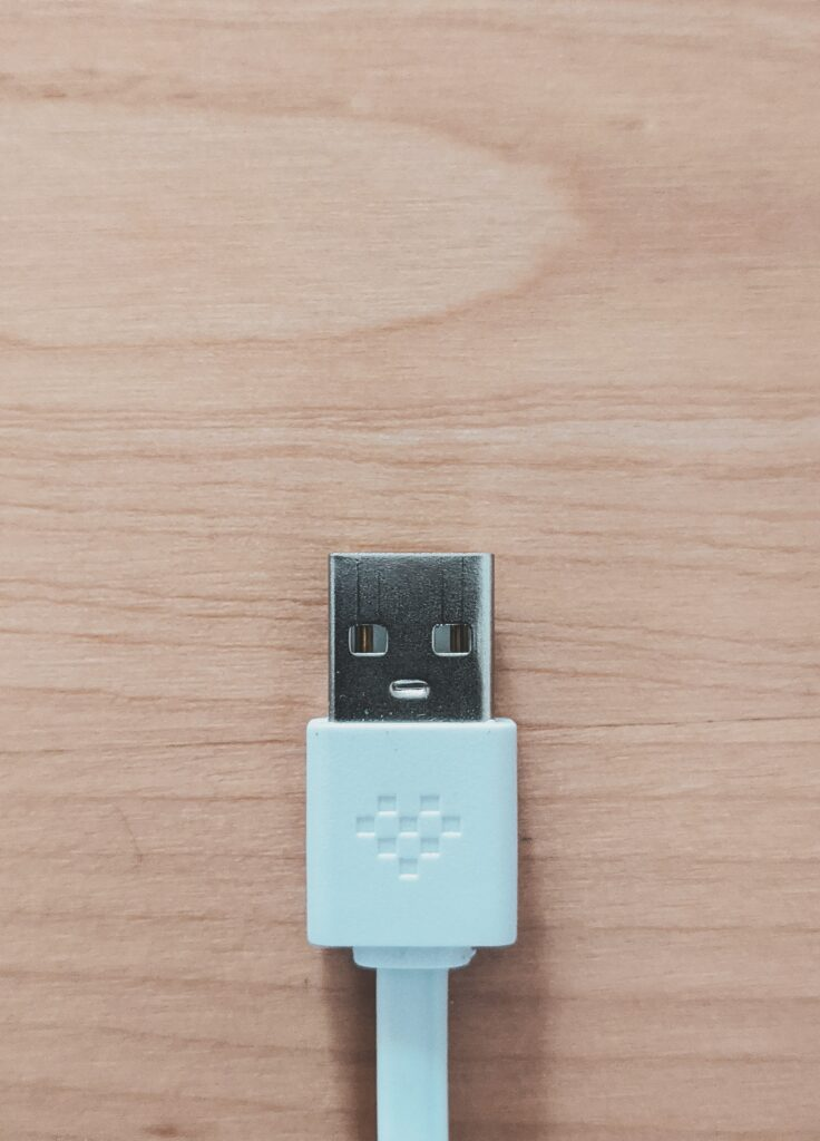 blue USB cable sitting on natural wood desk