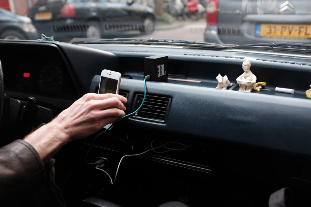 person plugging phone into phone car charger