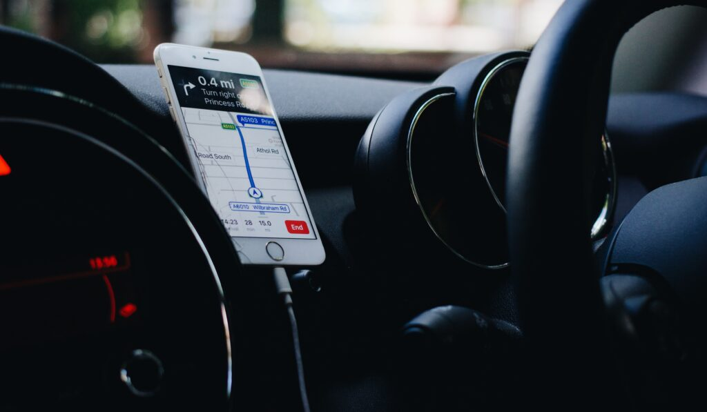 iphone with apple maps display on screen, plugged into a car charger