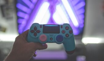 person holding a blue gaming controller in front of screen