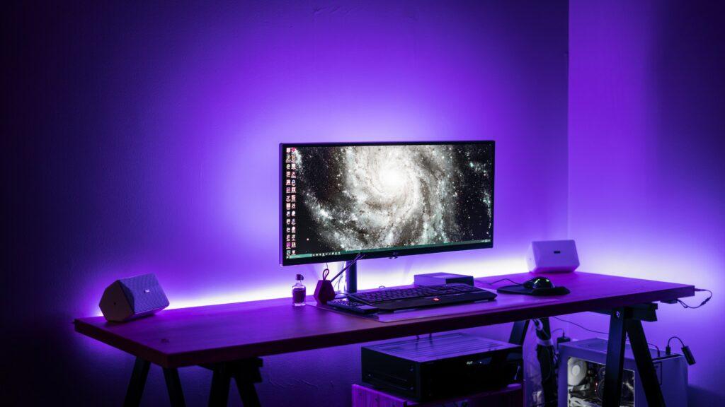 Widescreen desktop monitor sitting on desk with a purple backlight