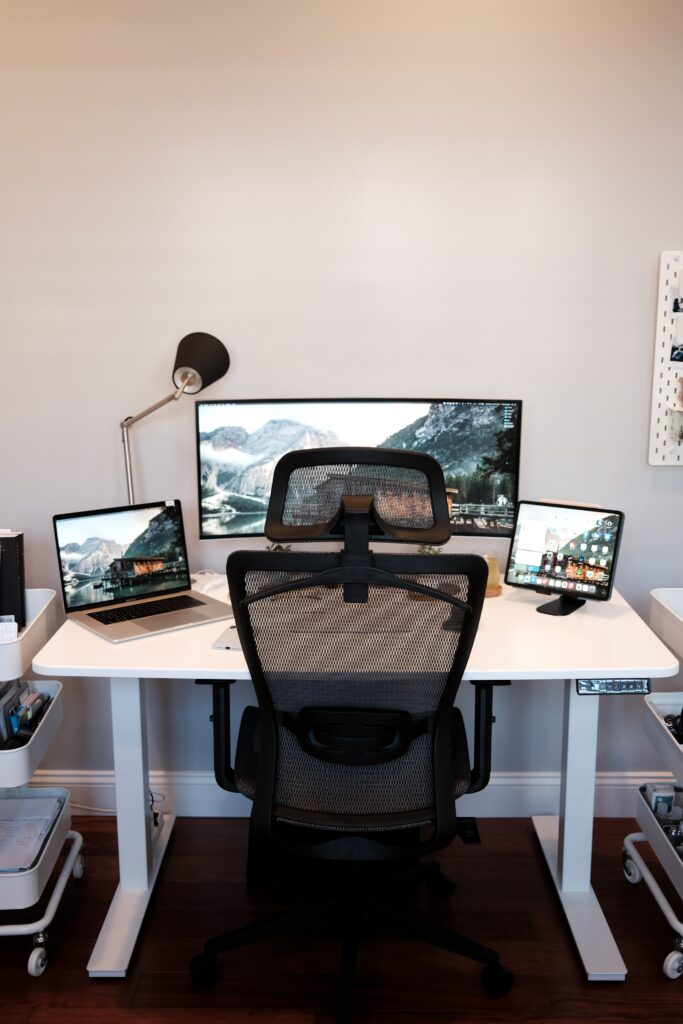 A view of a desk and chair, with a monitor, laptop, and tablet sitting on desk