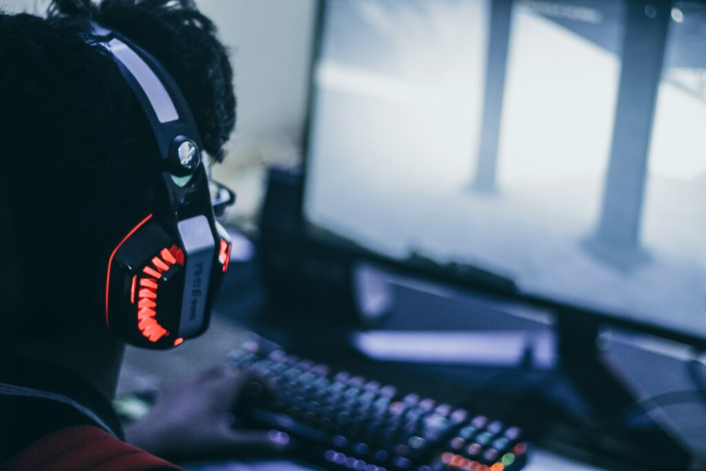person with headset on playing a video game on the computer