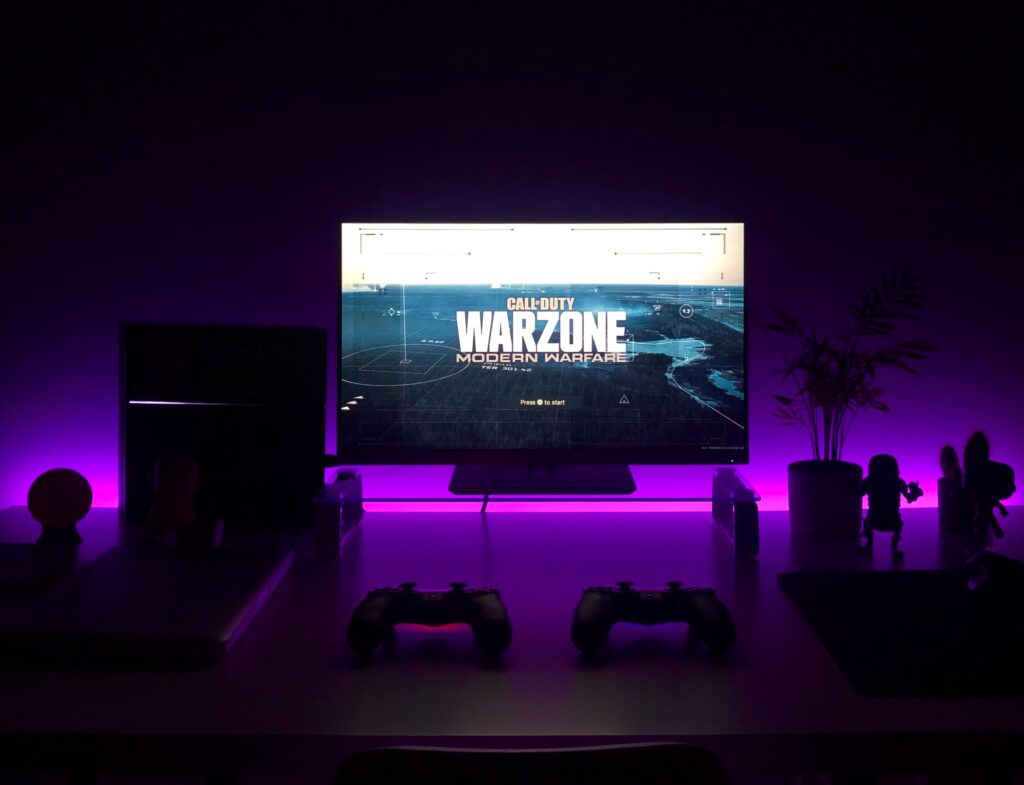 dark room with gaming computer screen lit up that has Warzone on the screen