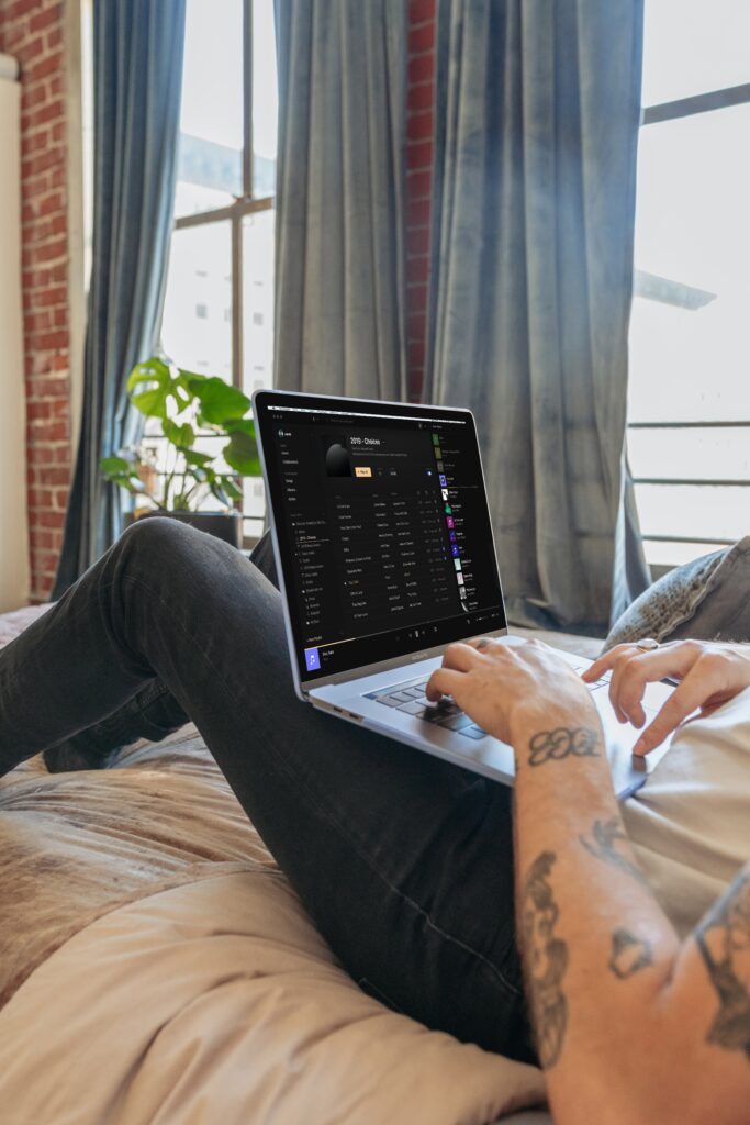 man sitting on couch working on laptop