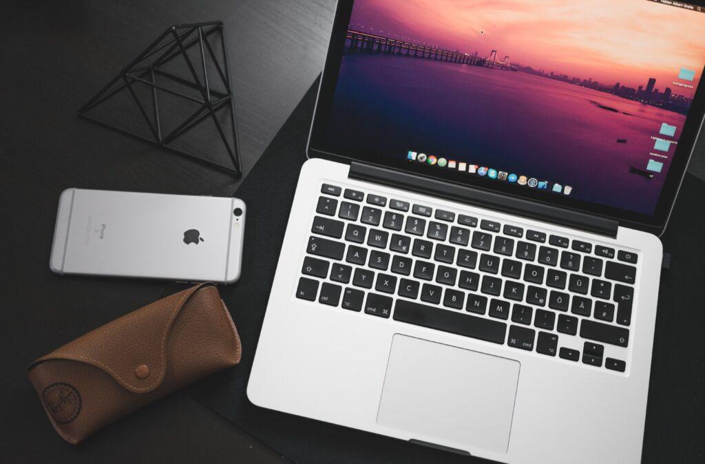 macbook laptop sitting on desk next to iphone