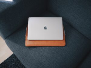 macbook sitting on case on a sofa