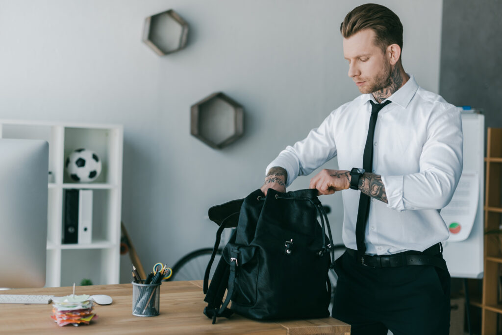 businessman putting his laptop away in his backpack