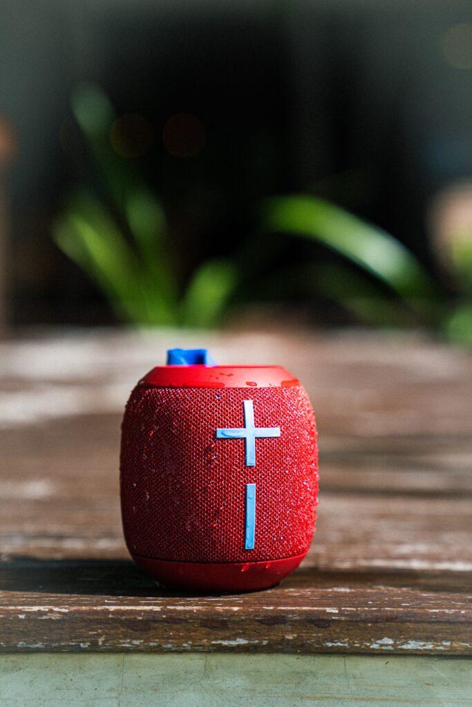 red JBL speaker sitting on ground outside