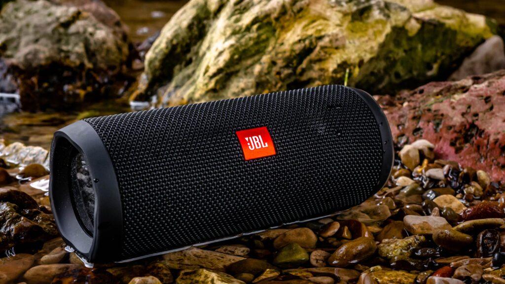 black JBL speaker sitting on ground outside
