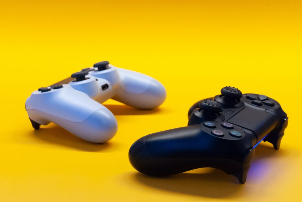 two controllers, one black and one white, sitting on a yellow table