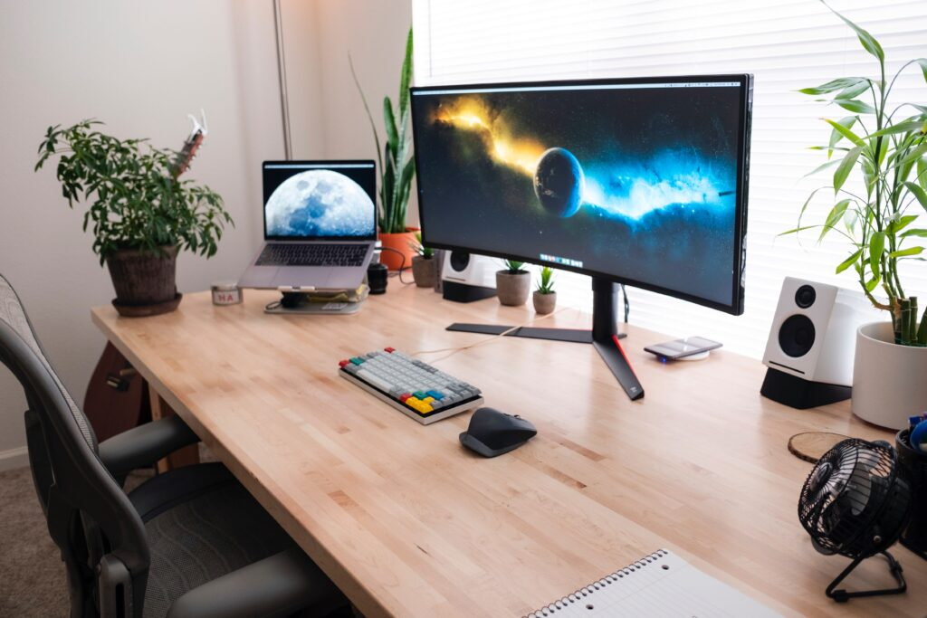 curved monitor sitting on desk next to laptop