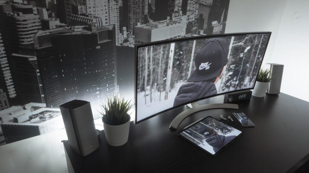 curved monitor sitting on black desk