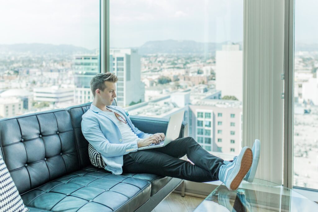 man sitting on couch working on his laptop