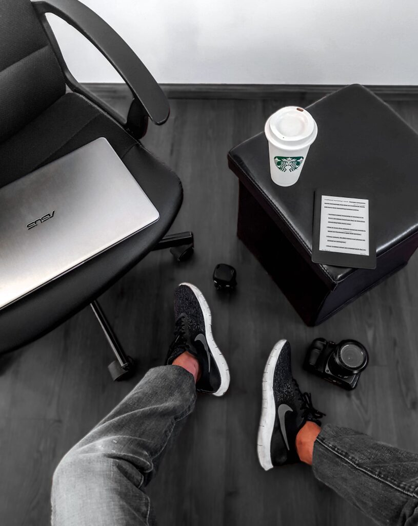 Top view of person sitting next to Asus laptop and a small end table with a coffee