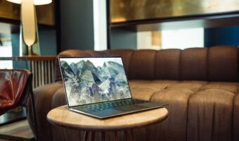 laptop with mountain background sitting on coffee table next to couch