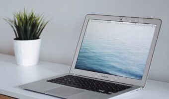 Laptop sitting on white desk next to small plant