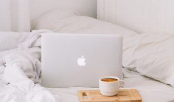 laptop sitting on white bed next to cofee mug