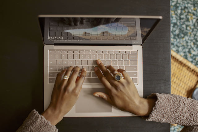 Top view of a woman typing on a laptop