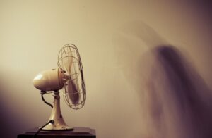 A moody scene of a small fan casting a shadow