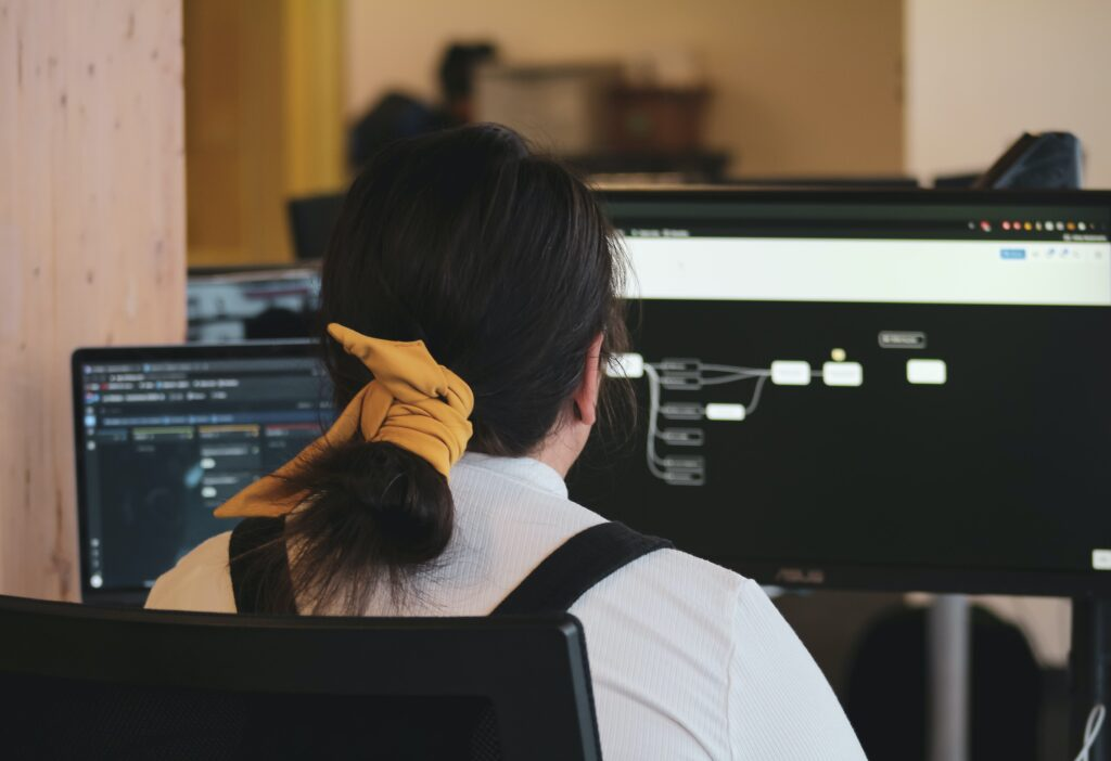 Girl with yellow hair tie looking at two screens working.