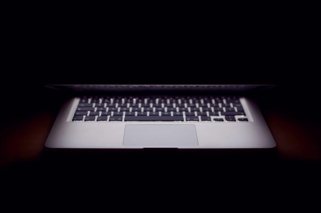 Laptop in dark room open halfway