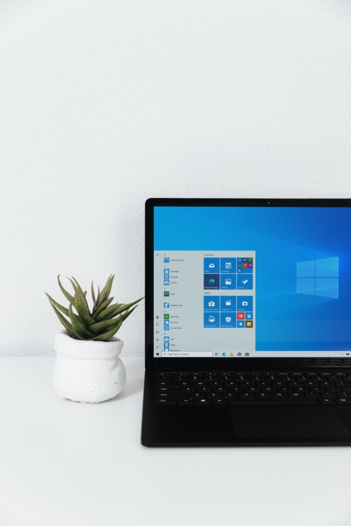 Windows laptop computer siting on desk next to plant