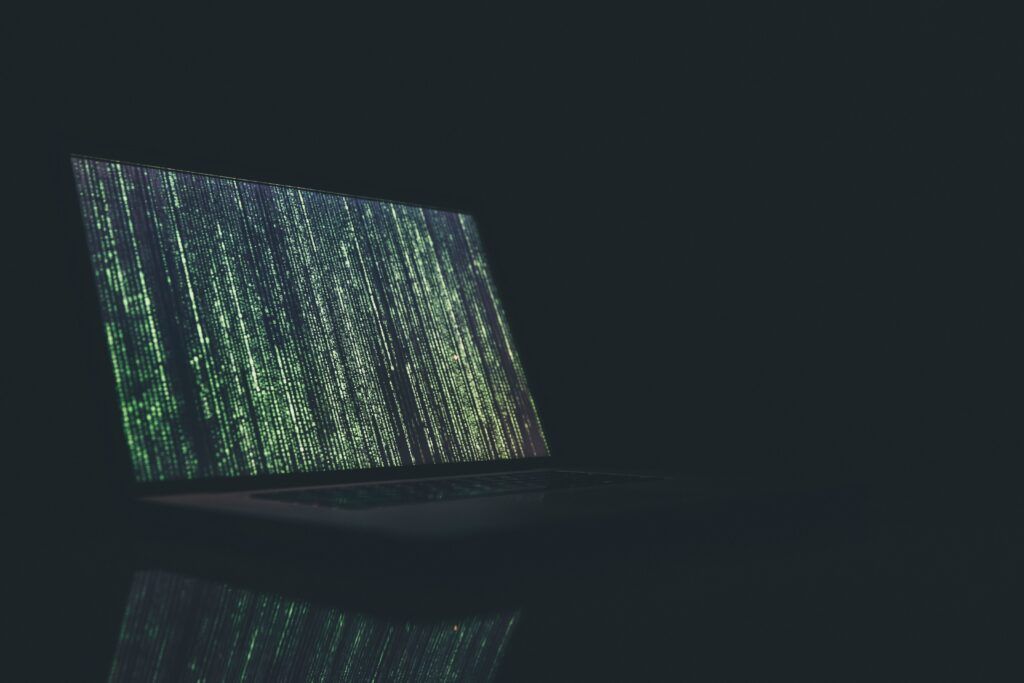 Laptop sitting in dark with green encryption codes on the screen